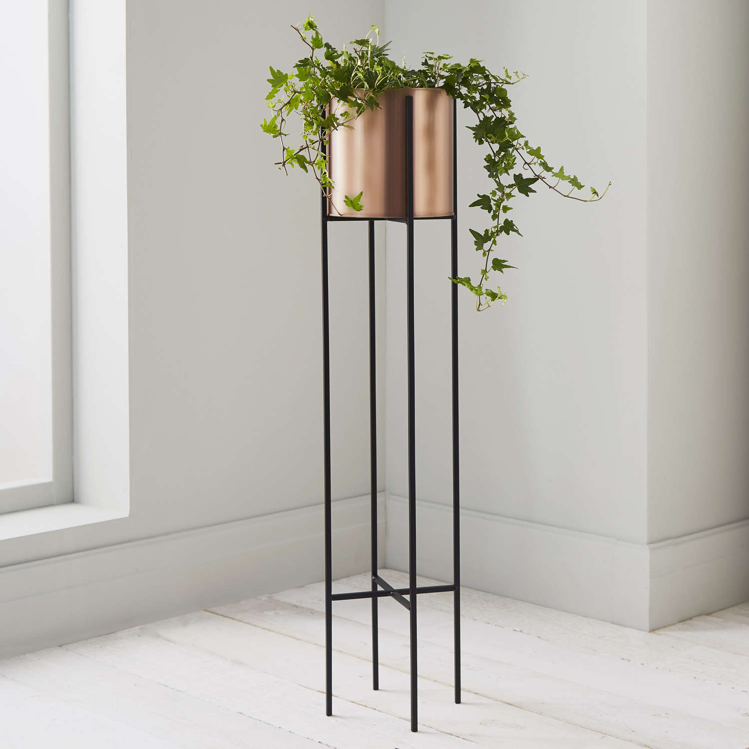 Round copper plant holder in black metal stand