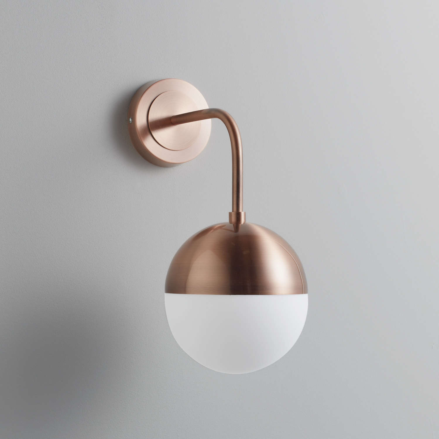Rose gold wall lamp with white glass globe