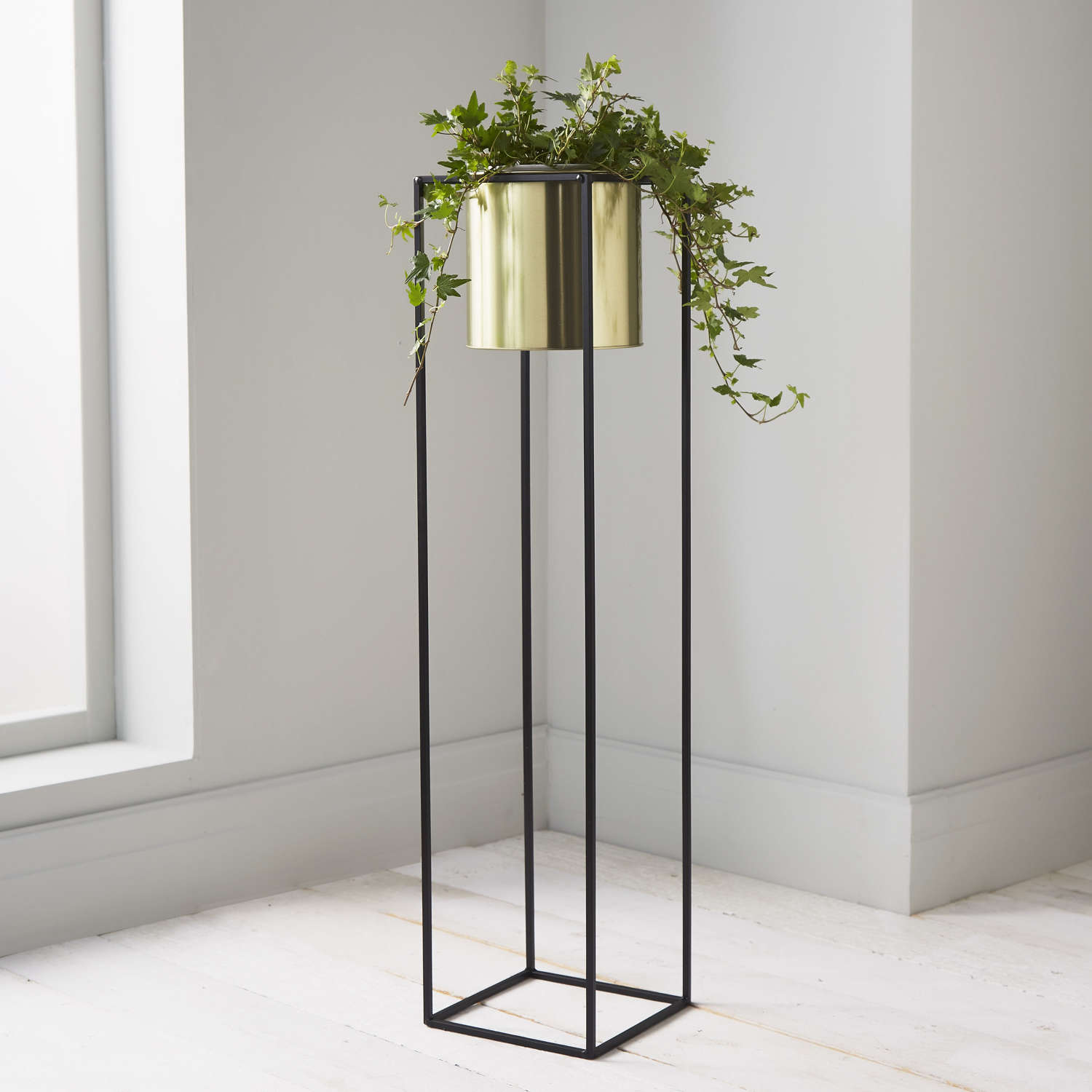 Round gold plant holder in square black metal stand